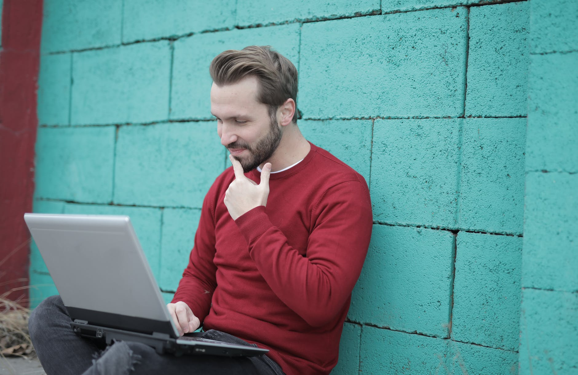 man in red long sleeve shirt using gray laptop computer